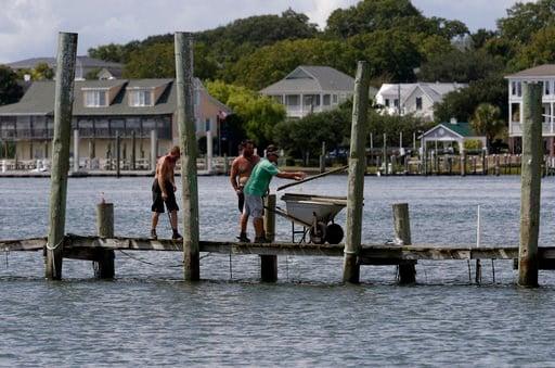 (AP Foto/Tom Copeland). (De izquierda a derecha) Josh Clappsy, Blake Price y JB Phillips retiran las tablas de un muelle con la esperanza de salvarlo de la crecida antes de la llegada del huracán Florence, en Swansboro, Carolina del Norte, el 11 de sep...